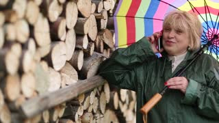 Blond woman with multicoloured umbrella in green waterproof coat stays near lumber and communicates via mobile phone. She holds smartphone in right hand and with umbrella in left hand