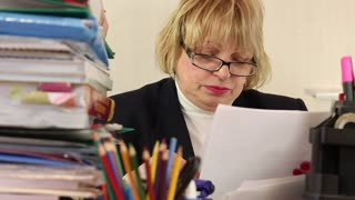Blonde woman chief financial officer in glasses and with commercial papers sits at the table in office. Bookkeeper with commercial papers. Trouble at work