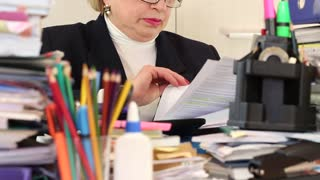 Blonde woman chief financial officer in glasses and with commercial papers sits at the table. Trouble at work. Bookkeeper with commercial papers