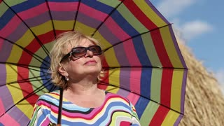 Blonde woman in glasses with brightly coloured umbrella stands near haystack and looks into the distance