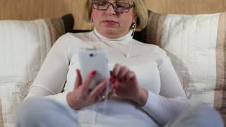 Blonde woman in glasses with white smartphone sits on the bed. Woman looks and flips through the photos in her smartphone. Female with smartphone. Elderly woman with mobile phone
