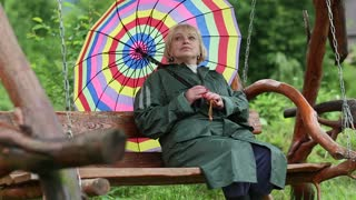 Blonde woman in green raincoat and with brightly coloured umbrella sits on the swing bench. Lady with umbrella