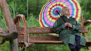 Blonde woman in green raincoat and with brightly coloured umbrella sits on the swing bench