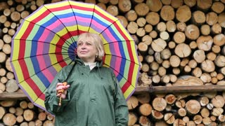 Blonde woman in green slicker with big multicoloured umbrella stands near lumber and smiling