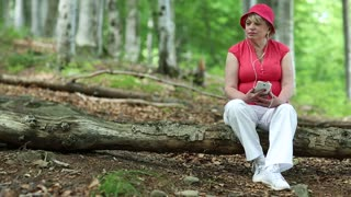 Blonde woman in red cap sits on a fallen tree in the forest and listens to music
