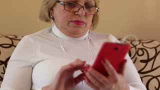 Blonde woman looking and flipping through the photos in her smartphone. Woman using red smartphone. The woman is shocked by what she saw