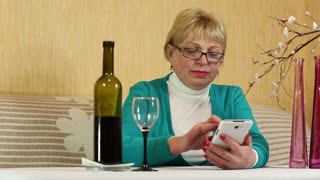 Blonde woman sits at the table, drinks red wine and speaks on smartphone. Female with smartphone. Woman pours red wine in goblet. Senior woman communicates via cell phone. Woman with wineglass