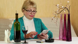 Blonde woman sits at the table, drinks red wine and talks on smartphone
