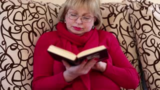 Blonde woman sits on a divan and reads a book. Female with book. Senior woman reads book