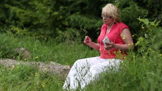 Blonde woman sits on a fallen tree in the forest listens to music and waving hands