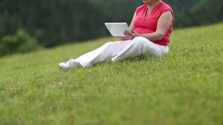 Blonde woman sits on a green grass and uses tablet computer. Woman with Tablet PC