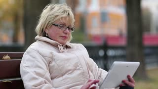 Blonde woman sits on the bench near traffic area and uses tablet computer. Woman with Tablet PC sits on the bench