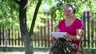 Blonde woman sits on the chair in garden and uses tablet computer. Senior woman with tablet pc sits under tree in garden. Female with tablet computer