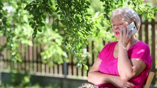 Blonde woman speaks on cell phone. Senior woman sits on the chair in garden and talks on smartphone. Female with smartphone. Businesswoman with smartphone sits under tree in garden