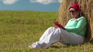 Blonde woman with red smartphone sits near haystack and listens to music. Senior woman in green t-shirt with red smartphone sits on the grass and listens to music