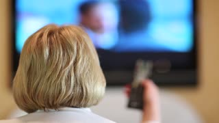 Blonde woman with remote control switch tv channels. Back of the head. Female watching television