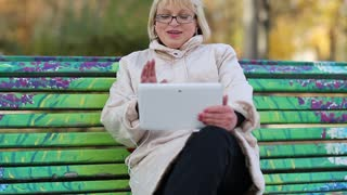 Blonde woman with Tablet PC sits on the bench and talks on Skype. Female with Tablet-PC. Senior woman sits on the bench near the road and communicates via tablet computer. She is in a merry mood