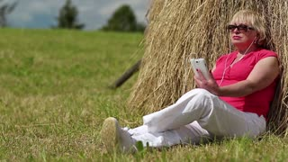 Blonde woman with white smartphone sits near haystack and listening to music. Senior woman in red t-shirt with white smartphone listening to music