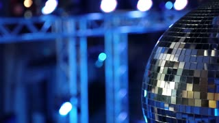Blue spinning glitterball on dancefloor