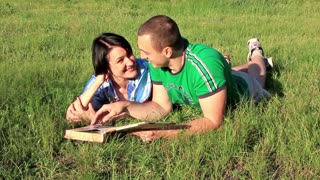 Boy and girl with photo album lying on the green grass