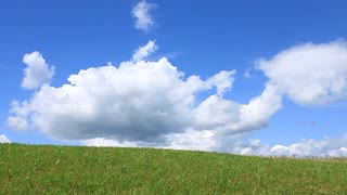 Boy going on green grass and sky background