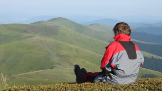 Boy siting on mountain before skydiving