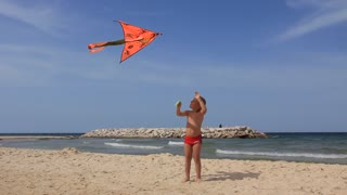 Boy with orange kite on the beach