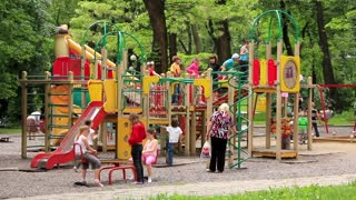 Boys and girls with parents on childrens playground
