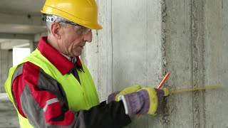 Builder in working clothes and yellow hard on construction site. Worker in yellow hard hat with yellow angle and pencil near concrete pillar