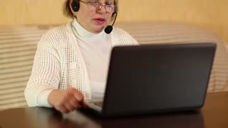 Businesswoman with headphones with microphone talks to a customer via computer. Woman communicates via laptop. Female with notebook. Woman with laptop. Woman with tablet pc communicates through skype
