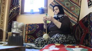 Carpet weaving. Aged turk woman with silk clew, carpet-makers. Weaving factory in Turkey