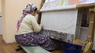 Carpet weaving. Turk woman, carpet-makers at weaving factory in Turkey