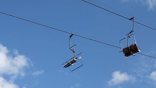 Chair lift on sky background