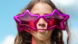 Cheerful girl in big glasses in shape of stars looks at camera and smiles. Funny little girl in big purple glasses looks into camera