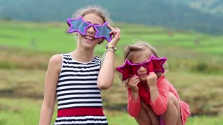 Cheerful girl in big glasses in the shape of stars looks at the camera and dance. Funny little girl in two pink and purple glasses looks at the camera