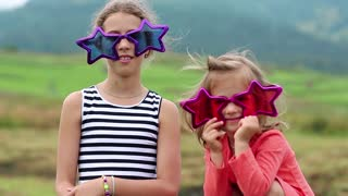 Cheerful girls in big glasses in the shape of stars looks at the camera. Two funny girls in pink and purple glasses looks at the camera and makes grimaces
