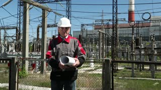 Chief architect with working drawings at heat power station. Worker in white hard hat with engineering drawing near outdoor switchgear at heat electropower station
