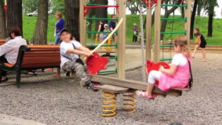 Childrens playground. Boy and girl on seesaw