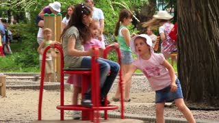 Childrens playground. Little girls on merry-go-round