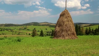 Clouds and haystack on a green field
