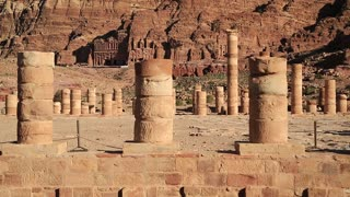 Columns of Great Temple in Petra - ancient historical and archaeological rock-cut city in Hashemite Kingdom of Jordan. Royal Tombs carved in the mountain on the background. UNESCO world heritage site