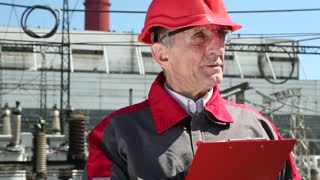 Construction engineer looks after building, wearing red and grey jacket and red helmet, writing down data in notebook