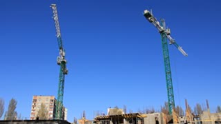 Construction site. Two big green crane on blue background