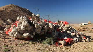 Construction waste lies in desert near Aqaba city in Jordan. Industrial plant on background. Building wastes lies on the nature