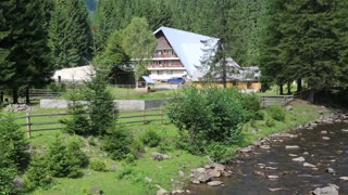 Cottage near mountain river in Carpathians, Ukraine