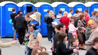 Crowd of people near outdoor public toilets