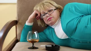 Depressed senior woman lying on a couch and drinking brandy