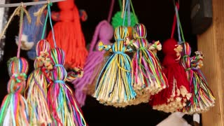 Dolls of women made of threads in souvenir shop. Colorful dolls hanging on strings