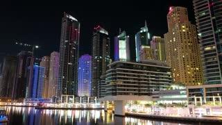 Dubai Marina night flip horizontal timelapse, United Arab Emirates. Dubai Marina - largest man-made marina in world. Dubai Marina is a canal city, carved along a 3 km stretch of Persian Gulf shoreline