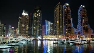 Dubai Marina night zoom timelapse, United Arab Emirates. Dubai Marina - largest man-made marina in the world. Dubai Marina is a canal city, carved along a 3 km stretch of Persian Gulf shoreline, UAE